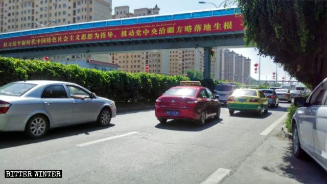 신장 자치구 우루무치(烏魯木齊)시의 선전 슬로건 포스터: 시진핑 주석의 생각을 받든, '신장 자치구를 통치하는 당 중앙 위원회 전략의 전면 시행을 촉진하라'