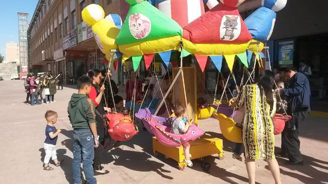신장 위구르 자치구의 대조적인 광경: 회전목마를 타며 놀고 있는 아이들 뒤로 허톈시(和田市) 시장의 '자경대원들'이 훈련을 하는 모습이 보인다.