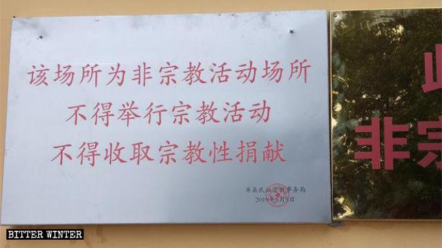 """사원의 동쪽 벽에 걸려있는 표지로 """"이곳은 종교 장소가 아닙니다""""라고 적혀있다"""