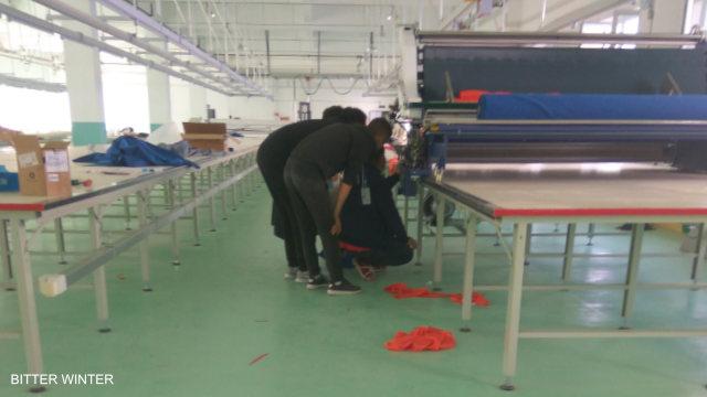 당국이 '적절한 일자리'라고 주장하는 강제 노역 공장들 중 한 곳에서 기계 테스트를 하고 있다