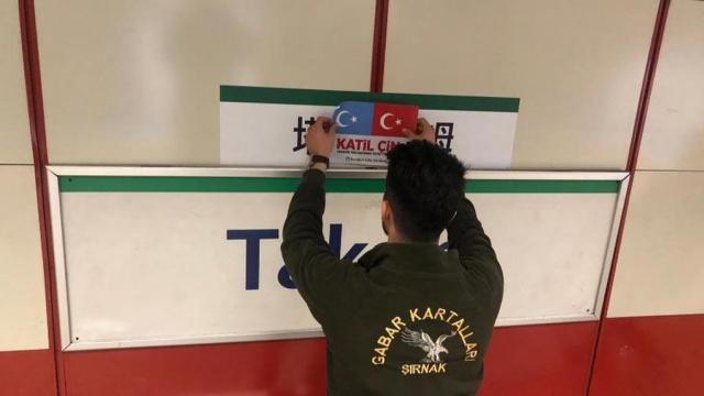 위구르인들을 지지하는 어느 터키인이 탁심(Taksim) 광장 전차역의 중국어 표기 위에 'katil çin' 즉, '학살자 중국인'이라는 글귀가 적힌 동투르키스탄과 터키의 깃발 문양의 스티커를 덧붙이는 모습