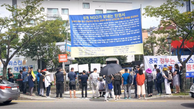 중공이 전능신교 신자들의 가족에 전문적인 시위꾼들을 섞어 조직한 일단의 사람들이 서울 소재 전능신교 건물 앞에서 집회를 벌이는 모습