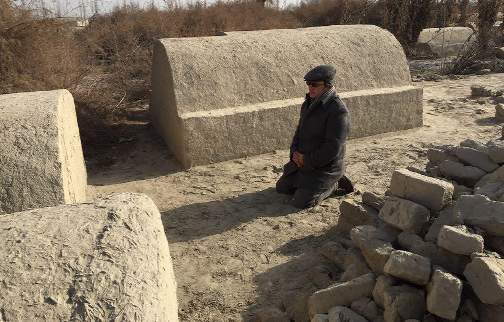 … 그러나 아지즈가 2012년, 파괴되기 전의 가족 무덤 앞에서 무릎을 꿇고 있는 모습을 담은 이 사진은 중국 정부의 선전이 거짓임을 증명한다.