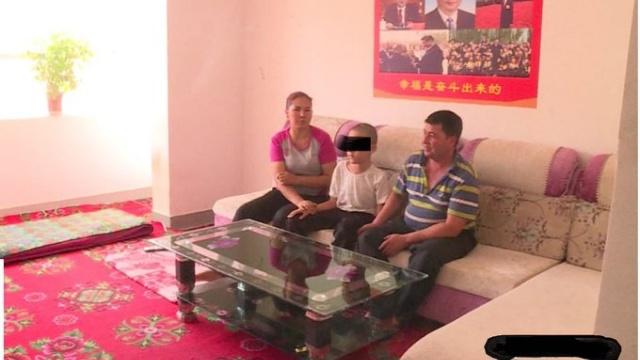 싸구려 소파와 탁자로 '중국화'된 위구르 가옥의 모습. 뒤로는 종교화가 걸려 있던 자리에 시진핑(習近平, 1953~) 초상화 포스터가 걸린 것을 볼 수 있다.