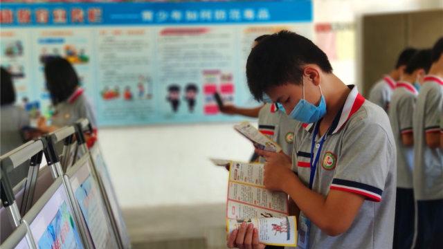 6월, 광둥성 언핑시의 한 학교에서 반사교 자료를 읽고 있는 어떤 학생